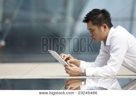 Homem de negócios asiáticos usando um touch pad PC