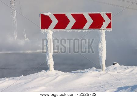 Frozen And Snowed Road Sign