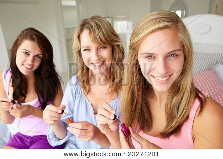 Mother and teenage daughters painting nails