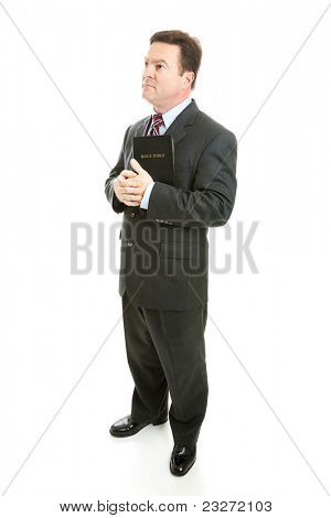 Pious minister or businessman holding his bible and looking thoughful.  Full body isolated on white.