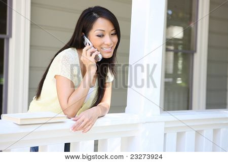 A pretty young woman on the cell phone on her home porch