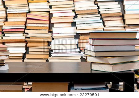 Books Piled Up Against Black Desk