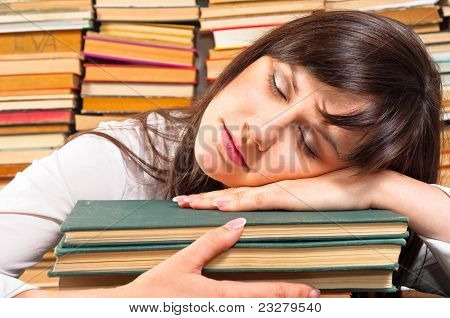 Overworked University Student Sleeping On Her Books