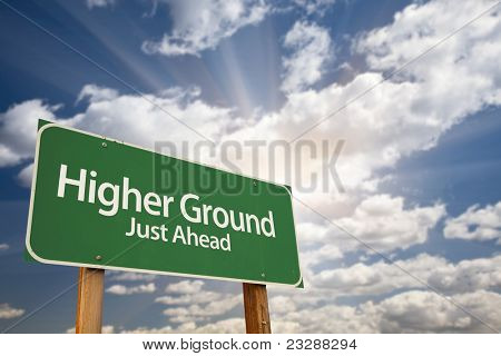 Higher Ground Green Road Sign Against Dramatic Sky, Clouds and Sunburst.