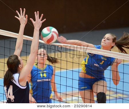 KAPOSVAR, HUNGARY - APRIL 24: Zsofia Harmath (3) strikes the ball at the Hungarian NB I. League woman volleyball game Kaposvar (blue) vs Ujbuda (black), April 24, 2011 in Kaposvar, Hungary.