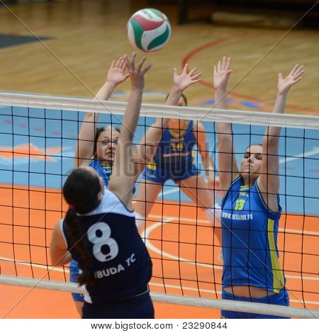 KAPOSVAR, HUNGARY - APRIL 24: Gabriella Kondor (13) blocks the ball at the Hungarian NB I. League woman volleyball game Kaposvar (blue) vs Ujbuda (black), April 24, 2011 in Kaposvar, Hungary.