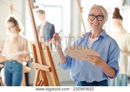 poster of Senior student or teacher of school of arts looking at camera while painting with oil colors