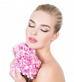 Young beautiful woman with flowers near face. Beauty treatment concept. Skin care. Pretty female wit poster