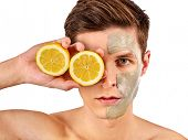 Facial mask from fresh fruits and clay for man concept. Face with treatment mud applied. Male holdin poster