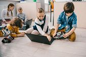 Kids Programming Robots With Laptops While Sitting On Floor, Stem Education Concept poster