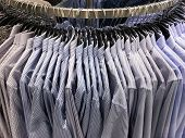 Clothes hang on a shelf . Cloth Hangers with striped Shirts. Mens business clothes  poster