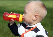 beautiful little boy drinking from red bottle