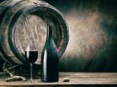 Glass of red wine and wine bottle. Oak wine keg at the background. poster