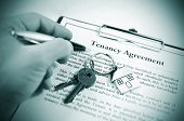 stock photo of rental agreement  - Hand signing tenancy agreement on clipboard with keys and symbolic house keyring - JPG