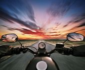 POV of motorbiker holding steering bar in beautiful sunset dramatic sky. Travel and freedom, outdoor poster