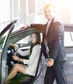 business woman sitting in the car,in the Parking lot at the car dealership. poster
