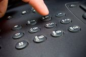 stock photo of dial pad  - closeup shot of a telephone keypad with finger dialing a number - JPG
