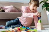 Child With Down Syndrome Playing With Toy Cubes On Floor In Cozy Room poster