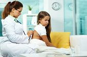 Portrait of serious clinician treating sick girl with stethoscope poster