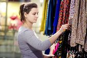 Young Attractive Brunette Girl Chooses Clothes In Trendy Boutique. Woman Is Buying New Clothes. Shop poster