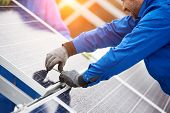 Smiling Male Technician In Blue Suit Installing Photovoltaic Blue Solar Modules With Screw. Man Elec poster
