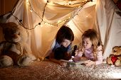 Little Kids Involving In Reading Amazing Book. They Lying In Nice Toy Tent In Playroom. Boy Holding  poster