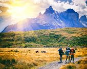Group Of Travelers With Backpacks Walk Along A Trail Towards A Mountain Ridge.backpackers Style. Con poster