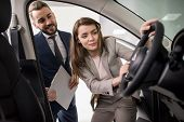 Portrait Of Beautiful Young Woman Looking Inside Car While Choosing Luxury Car In Dealership Showroo poster