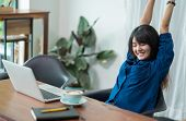 Asia Woman Relax After Working,female Raise Arm Up Stretching In Front Of Laptop And Coffee Cup On W poster