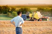 Engineer With Notebook And Combine Harvester In Field poster