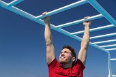 Fitness monkey bars man training arms muscles on jungle gym outdoors in summer. Athlete working out  poster