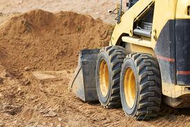 stock photo of skid-steer  - Closeup skid steer loader excavator at road construction work - JPG