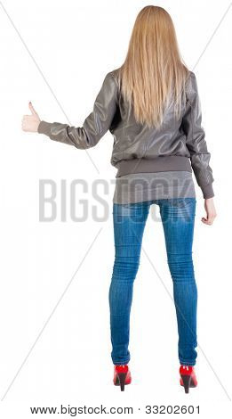 back view of standing young blonde woman showing thumb up. beautiful girlgesturing ok sign. Rear view people collection.  backside view of person.  Isolated over white background