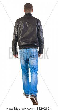 Vista traseira do passeio homem bonito na camisa.   vai cara jovem, de jeans e casaco. Traseira vista pesso