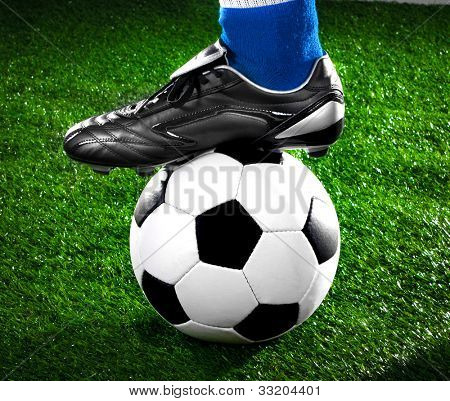 soccer payer withl with his foot on the football field