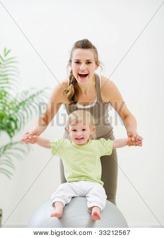 Mother Mother Holding Baby Sitting On Fitness Ball