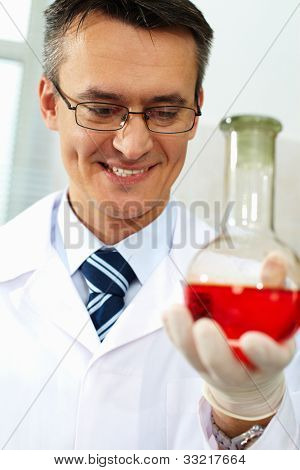 Male scientist in eyeglasses holding glassware with new substance