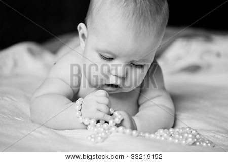 Infant Girl Plays With Enthusiasm Pearl Beads Lying On Tummy