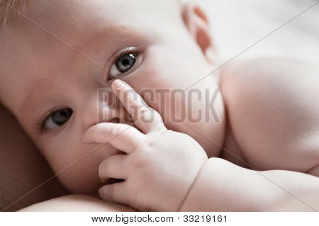 Infant Lies In Her Mother's Breast And Closes Her Palm Face