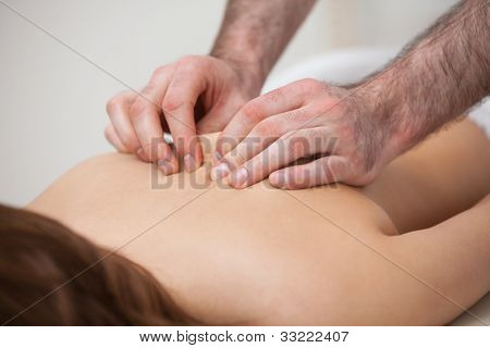 Chiropractor massaging his patient while using his fingertips in a room