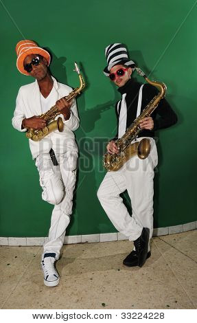 Portrait of two young male funky musicians with saxophones