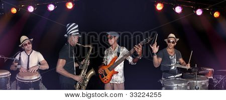Portrait of four musicians playing on stage against black background