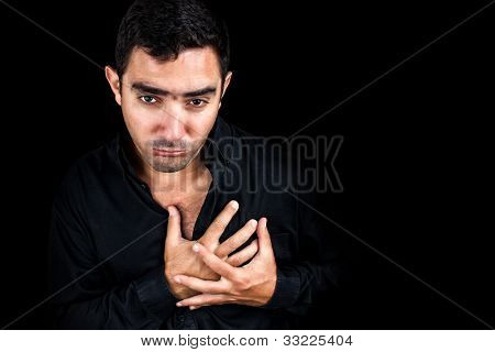 Dramatic image of a young man having a very painful heart attack bending over and clutching his chest isolated on black