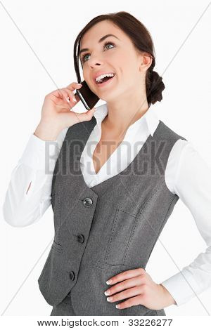 Happy well-dressed woman calling with a smartphone against white background