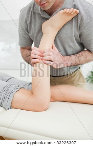Close-up of a man massaging the leg of a woman in a room