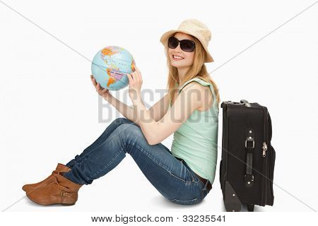 Woman holding a world globe while smiling against white background