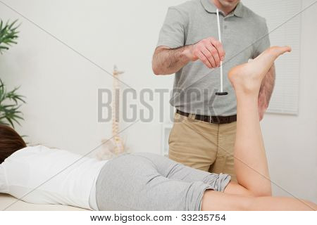Serious doctor using a reflex hammer on his patient in a medical room
