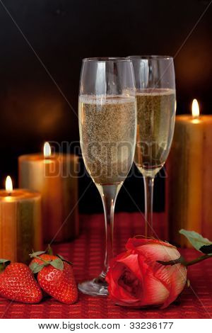 Glasses of champagne with strawberries and a rose beside candles on a red tablecloth against a black background