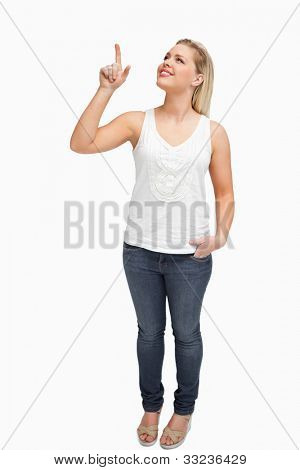Joyful blonde woman pointing her finger up against a white background