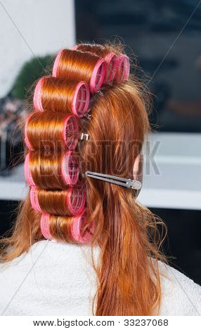 Closeup of red hair during hair dressing with curler